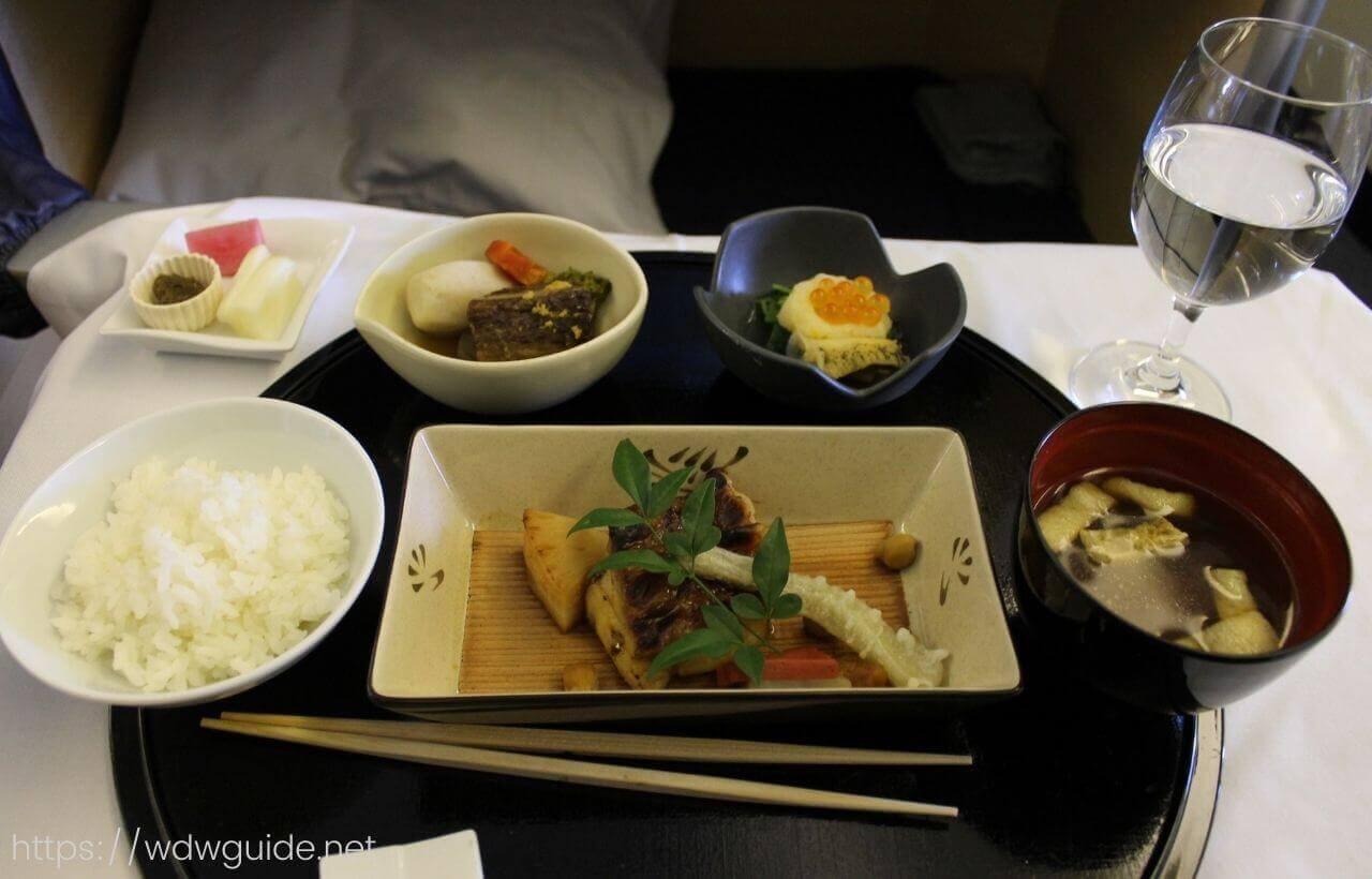 ANAファーストクラスの炊き合わせと小鉢、主菜にごはん、味噌汁、香の物
